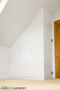 Contemporary MDF sloping wardrobe fitted in the loft spare room.