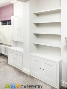 Alcove fitted TV cabinets with bookshelves besides the chimney